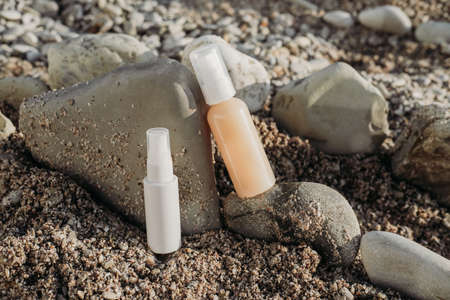 Cosmetic serum bottles on natural stone on the beach. sea natural background, concept of natural skin care products. Skincare essence for beautiful healthy skin. sunscreen lotion.