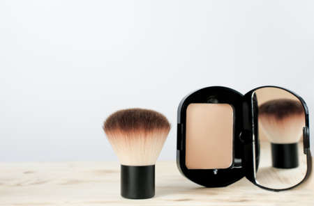 compact foundation powder with brush. beauty product for women. brush reflection in the mirror.