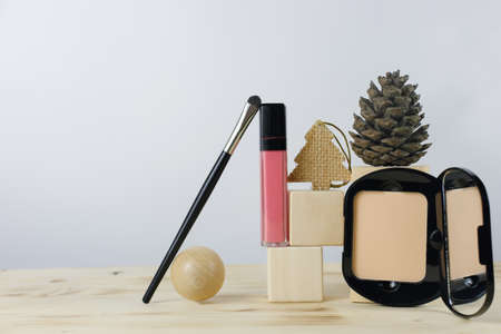 Pink lipstick on a wooden stand and face powder. Christmas gift for women. Beauty tools accessory for professional makeup for a make-up artist. Festive decoration of cosmetic products. Copy space.