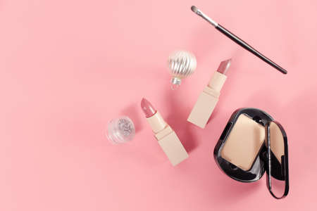 set with makeup products and Christmas decor on pink background. Space for text. holiday gift for women. lipsticks, compact powder and shining balls.