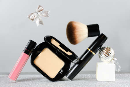 set of professional decorative cosmetics, makeup beauty, fashion and shopping concept. christmas gift. face powder, lipstick, brush and mascara with christmas ball and ribbon bow