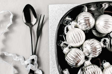 Christmas table setting. Christmas tree balls on a black plate, knife, fork. Top view, flat lay. The concept of Christmas and the new year. silver monochrome composition