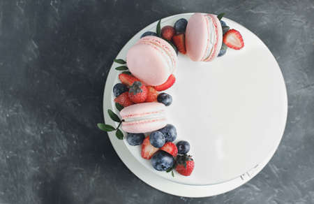 top view of a beautiful white mousse cake decorated with pink macarons and fresh strawberries and blueberries on gray background.