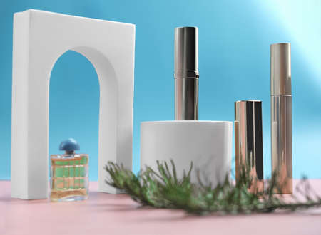 set of cosmetics on pink and blue background with white podium display and christmas tree branch. gift for woman. shiny mascara, lipsticks and perfum near trendy arch