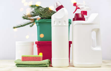 Christmas cleaning. Cleaning tools and Christmas decorations. housekeeping before holidays, bokeh lights, bottles of detergents and sprays. rug and sponge. Stock fotó