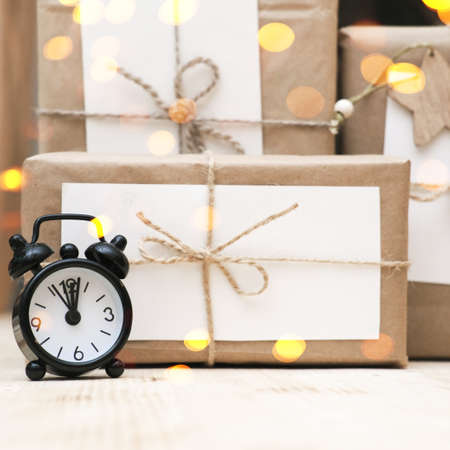 hand made christmas gifts wrapped in craft paper and alarm clock. bokeh lights. christrmas celebration time. sustainable holiday gifts.