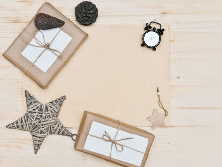 Zero waste Christmas flat lay. stylish simple christmas gifts in craft paper on rustic white table with christmas star and pine cones. alarm clock. Plastic free sustainable lifestyle. Stock fotó