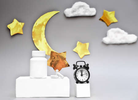 healthy sleep concept. medical capsules and alarm clock on white pedestal. melatonin and circadian rhythms. unbranded bottle with sleeping pills. moon and stars background.