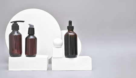 unbranded cosmetic bottles on white podium or pedestal. brown dispenser bottles with cosmetic cream or lotion. self care spa concept. minimal trendy geometric style composition.copy space for text.