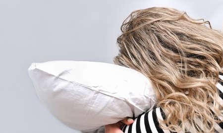 cyrcadian rhythms, melatonin and teenagers healthy sleep. curly teenager girl hugging a pillow. unrecognizable girl in striped pijama sleeping tight.