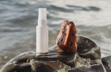 beauty treatment medical skincare and cosmetic lotion. white cream serum mockup bottle. sea mineral ingredients product on a stone beach background, sensitive skin care.