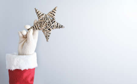 santa's hand holding a christmas star. christmas decoration. copy space for text.
