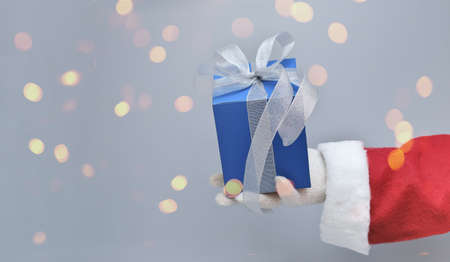 santa's hand holding blue christmas gift with silver ribbon bow. present for men. gray background, bokeh lights. holiday celebration.