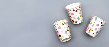 festive recycled paper cups on gray background. Zero waste concept. drinking holiday disposable cups for birthday or anniversary celebration. multicolored cardboard mugs. copy space, banner.