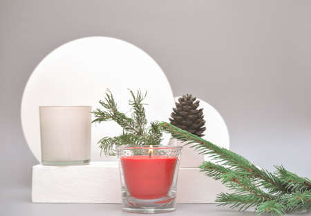 New Year design with two candles and christmas tree. pine cone and geometric shapes podiums on gray background. copy space.