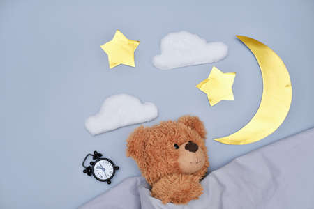 teddy bear sleeping under blanket on gray background. moon, stars and alarm clock. kids healthy sleep concept. cyrcadian rythms and good night time for children