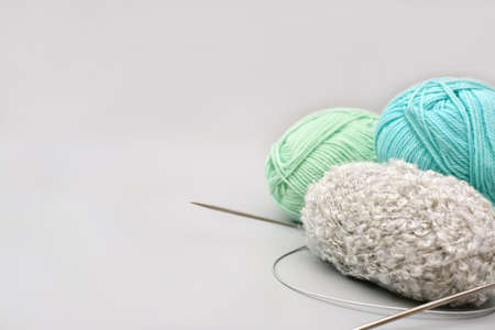 variety of knitting yarn and needles on gray background. needlecraft and winter hobby. needlework and hand made clothes concept. blue, green and gray skeins of yarn.