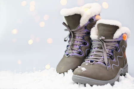 Pair of woman suede gray boots on snow in winter sunny day. Concept of winter outfit. warm boots for cold season. bokeh lights. Copy space. Stock fotó