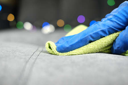 close up view of a Hand in protective glove cleaning sofa with rag. christmas cleaning or clean up. Maid cleans furniture in a house.