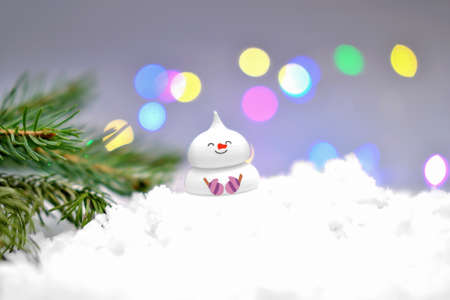 cute edible snowman on the snow and christmas tree branch. bokeh lights. holiday selebration and merry christmas, sugar candy snowman for cake top. Stock fotó
