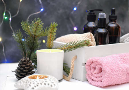 Fresh pink towel rolled on wooden table, candles and spa cosmetic bottles. holiday Hotel spa and wellness concept. christmas self care and relax time.