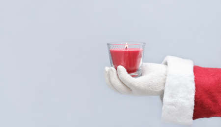 santa's hand holding a christmas red candle. christmas mood, scented soy candle. copy space for text. home selebration. Stock fotó