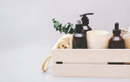 set of spa products for skin care in wooden box. unbranded brown bottles for beauty and relax. Scented candle and natural exfoliating washcloth and sponge. copy space.