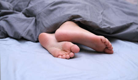 girls toes covered with bed sheet. crop view of a girl in the bed Stockfoto