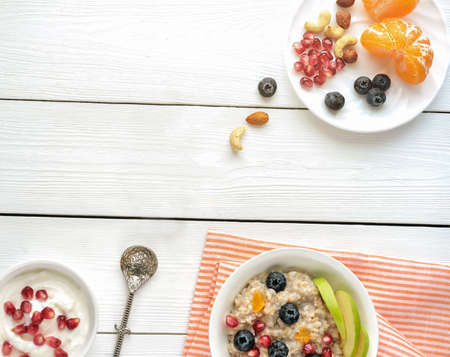 Breakfast, oatmeal with blueberry orange and nuts in white bowl in the morning. porridge with orange and pomegranate seeds. healthy breakfast.