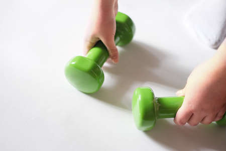 teenage girl hand holding green dumbbels. Healthy lifestyle, sport and home workout concept. Close up view