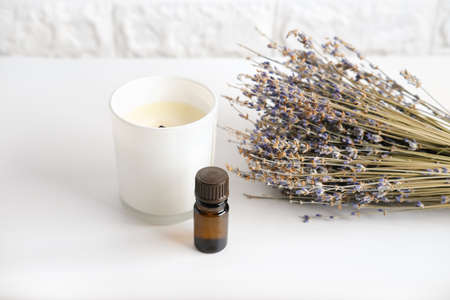 natural relax and good sleep assistants. scented candle, lavender flowers and lavender essential oil. natural way to relax before sleep.