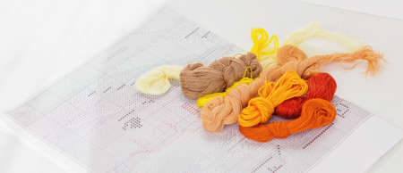 color threads for embroidery and printed scheme on a white table. hobby and leisure for relaxation and mind balance. banner size. set of multicolored floss.