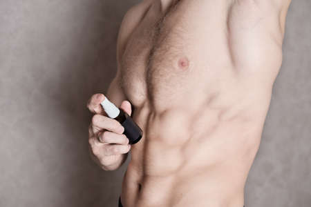 toned muscular man using body deodorant for freshness and confidence all day long. natural antiperspirant deo spray for men. shirtless fit young person, crop view