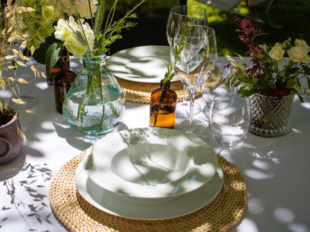 Beautiful decorated dining table with floral decor, plates, tablecloth in the garden. Party in the garden. High quality photo