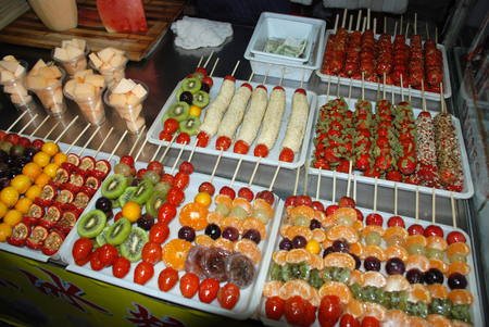 Fresh fruits on the stick covered with melted sugar