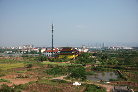 Chinese village view with yellow temple and big antena nearby, the blury look of the city buildings on the background
