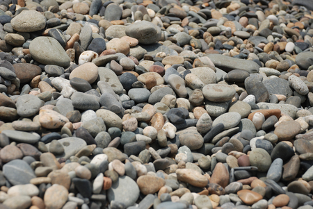 Pebbles of different shape, size and color on the beach on the sunny day