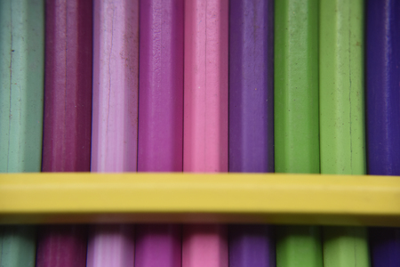 Turquoise, fuchsia, light pink, rose pink, pink, violet, green, dark blue pencils under the yellow pencil Imagens