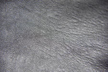 Close up photo of black leather with visible pattern of the texture