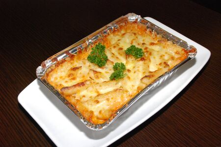 Lasagna in the foil on the white plate