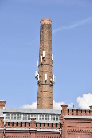 old factory chimney with modern antennas on it