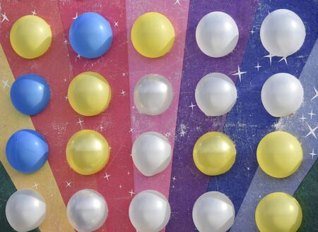 white and yellow balloons on the rainbow colored board