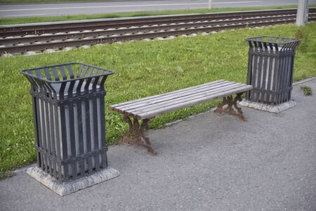 small wooden bench near railways in the city