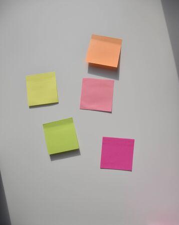 yellow, pink, orange, green stickers on the white board Фото со стока