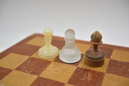 wooden, glass and plastic ponces on the chess board on white background Фото со стока