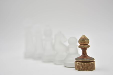 glass chess figures behind wooden ponce on white background Фото со стока