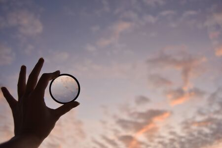 silhouette of female hand holding the lense  and the blue sky on the background at the time of the sunset