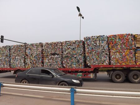 The track with pressed  colorful cubes of garbage on the highway Фото со стока