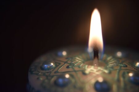 burning white candle with green ornament and pearls on the dark background Stockfoto - 131217382