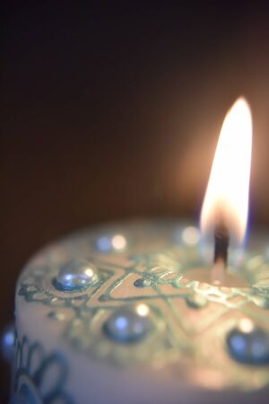 burning white candle with green ornament and pearls on the dark background Stockfoto - 131225555